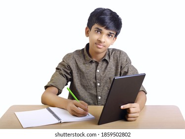 Indian boy using digital tablet while attending the online classes at home