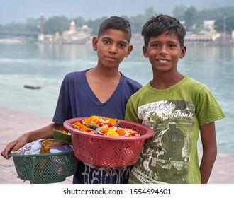 Indian boys selling flowers on the waterfront in Rishikesh, Uttarakhand, India. 30.10.2019