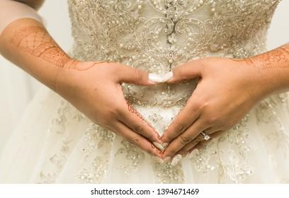 Indian bridal making a heart shape and Mehndi design