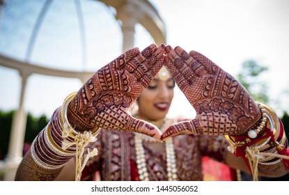 Indian bridal making heart shape and showing mehndi design her wedding day Lahore, Pakistan, July 01, 2019