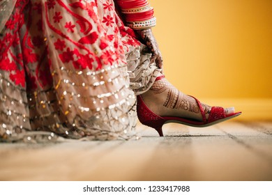 Indian Bridal showing High heels Sandals shoes and showing foot mehndi design
