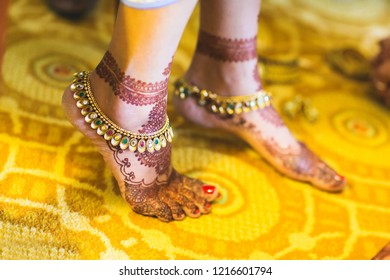 Indian bridal wearing gold payal anklets and showing foot mehndi design