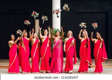 Indian bride and bridesmaids through their bouquets up