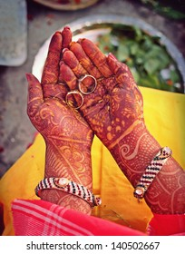 Indian bride doing ring rituals with henna on hands