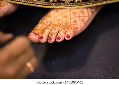 Indian bride feet coloring with indian henna paste or mehndi design of symbolic tattoos during a Hindu wedding ceremony - Image