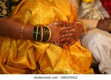 Indian Bride with finger crossed seating with golden saree and heena mehendi Green Glass Bengals