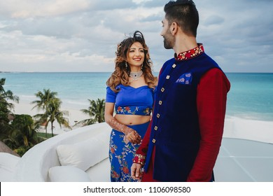 Indian bride and groom dressed in traditional clothes stand on the white porch in cloudy weather