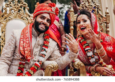 Indian bride and groom dressed in traditional shewrani, lehenga and with flower garlands on their necks sit on the chairs during Hindu wedding ceremony and show their hands with wedding rings
