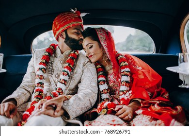Indian bride and groom dressed in traditional shewrani, lehenga and with flower garlands on their necks sit inside the car after wedding ceremony