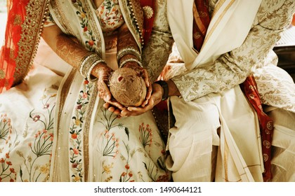 Indian bride and groom holding coconut at ritual ceremony