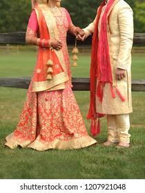 Indian bride and groom Holding hand showing wedding lehnga sharara and sharwani
