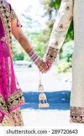Indian bride and groom holding hands in traditional outfit.