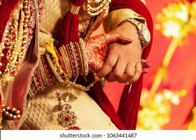An Indian bride and groom holding their hands during a Hindu wedding ritual. Close up view, selective focus.