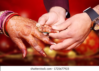 An Indian bride and groom holding their hands during a Hindu wedding ritual ring ceremony program