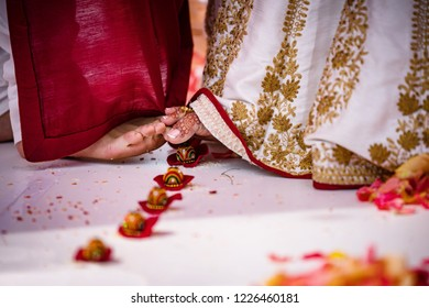 Indian bride and groom rolling betel nuts with toes