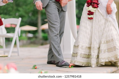 Indian bride and groom rolling betel nut with toes