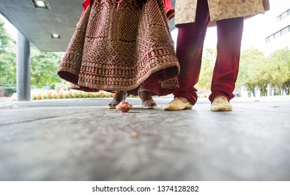 Indian bride and groom in touching the seven betel nuts with her toe during the Saptapadi ritual ceremony