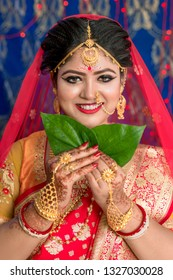 Indian bride hiding her face with betel leaf also called paan. Hiding with paan leaf by the bride is must Hindu wedding rituals in Bengali wedding.