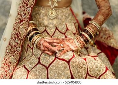 Indian bride holds her hands with lots of bracelets over her golden lehenga