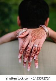 Indian bride hugging to groom and showing mehndi design