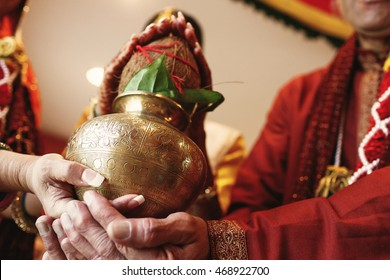 Indian bride puts a bronze bowl with coconut over her parents hands