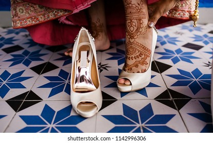 Indian bride putting shoes and showing foot mehndi tattoos