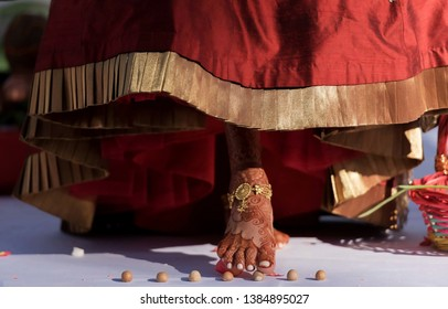 Indian bride in touching the seven betel nuts with her toe