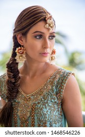 Indian bride wearing traditional clothing and jewelry in tropical location with bright skies