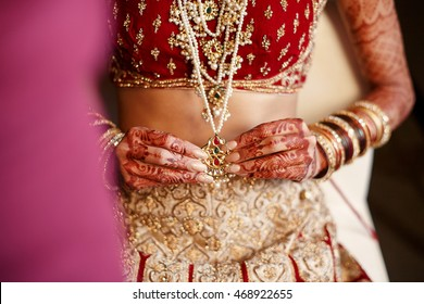 Indian bride's long finders hold a golden pendant hanging over her red costume