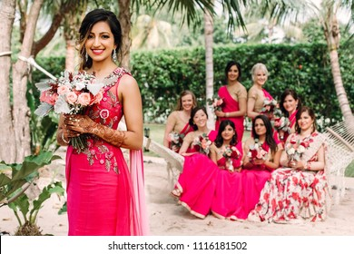 Indian bridesmaids admire beautiful bride posing together in the garden