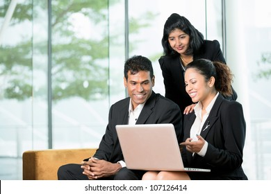 Indian Business colleagues working together around a laptop