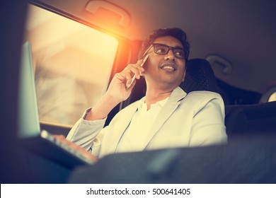 indian business male using laptop and phone inside the car