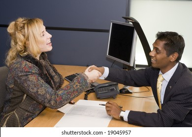 Indian Business Man and Caucasian Woman Handshaking on a Deal