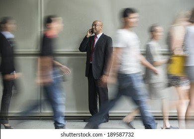 Indian Business man using a Cell Phone with People walking past in a rush.