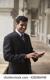 Indian business Man using his Smart phone outdoors in Asian city.