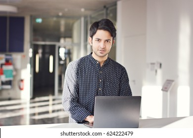 Indian business man working on laptop sitting on desk
