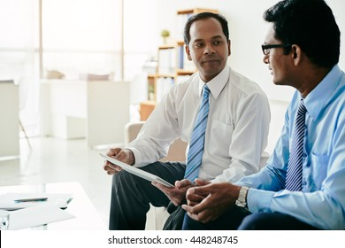 Indian business people discussing information on tablet computer