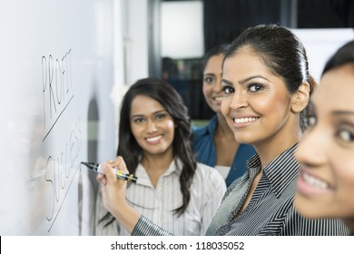 Indian business woman writing 'success' on a whiteboard with her team around her.