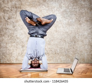 Indian businessman doing yoga headstand pose and looking at his laptop in the office at brown textured background