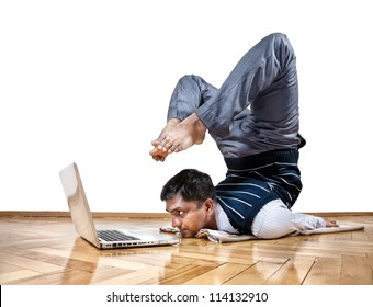 Indian businessman doing yoga and looking at laptop in the office at white background. Free space for your text