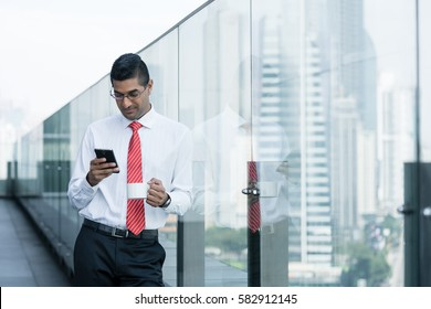 Indian businessman drinking coffee and using a smartphone on the terrace of a modern building