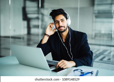 Indian businessman in earphones with laptop computer working at office and listening to music