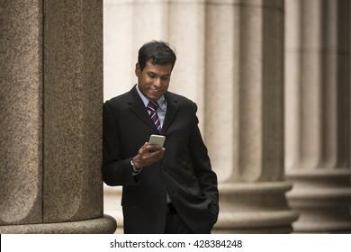 Indian businessman or Lawyer using a Smart Phone outside a colonial courthouse building.
