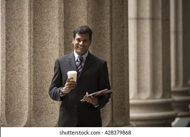 Indian businessman. Professional Lawyer or business man outside a colonial courthouse building.