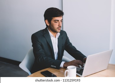 Indian businessman searching information and application for making productive presentation in corporate company using netbook at desktop, handsome guy wear in formal suit jacket reading news online