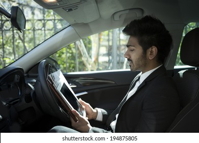 Indian businessman sitting in his parked car and using Tablet PC.