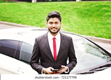 Indian businessman with smartphone standing near car outdoors