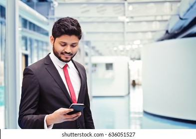 Indian businessman with smartphone standing at the office
