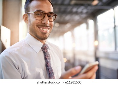 Indian businessman smiling confidently and surfing the net on a smartphone