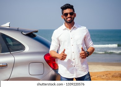 Indian businessman standing near car outdoors on sea beach summer good day.a man in a white shirt and snow-white smile rejoicing buying a new car enjoying a vacation by the ocean